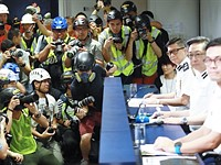 Hong Kong photojournalists attend press conference in riot gear following protests